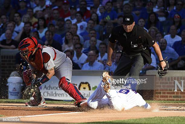 Chris Coghlan of the Chicago Cubs is safe at home as Yadier Molina of the St Louis Cardinals takes a late throw during the first inning on June 21...