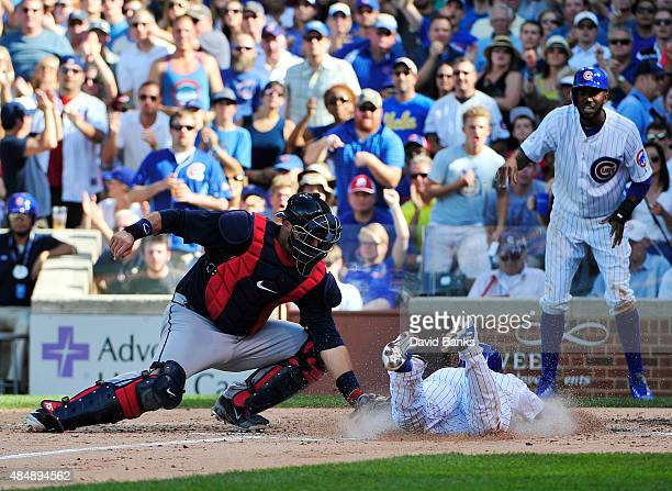 Chris Coghlan of the Chicago Cubs is safe at home plate as AJ Pierzynski of the Atlanta Braves makes a late tag during the fifth inning on August 22...