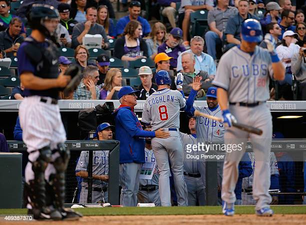 Chris Coghlan of the Chicago Cubs is welcomed to the dugout by manager Joe Maddon of the Chicago Cubs and Dave Martinez of the Chicago Cubs after his...