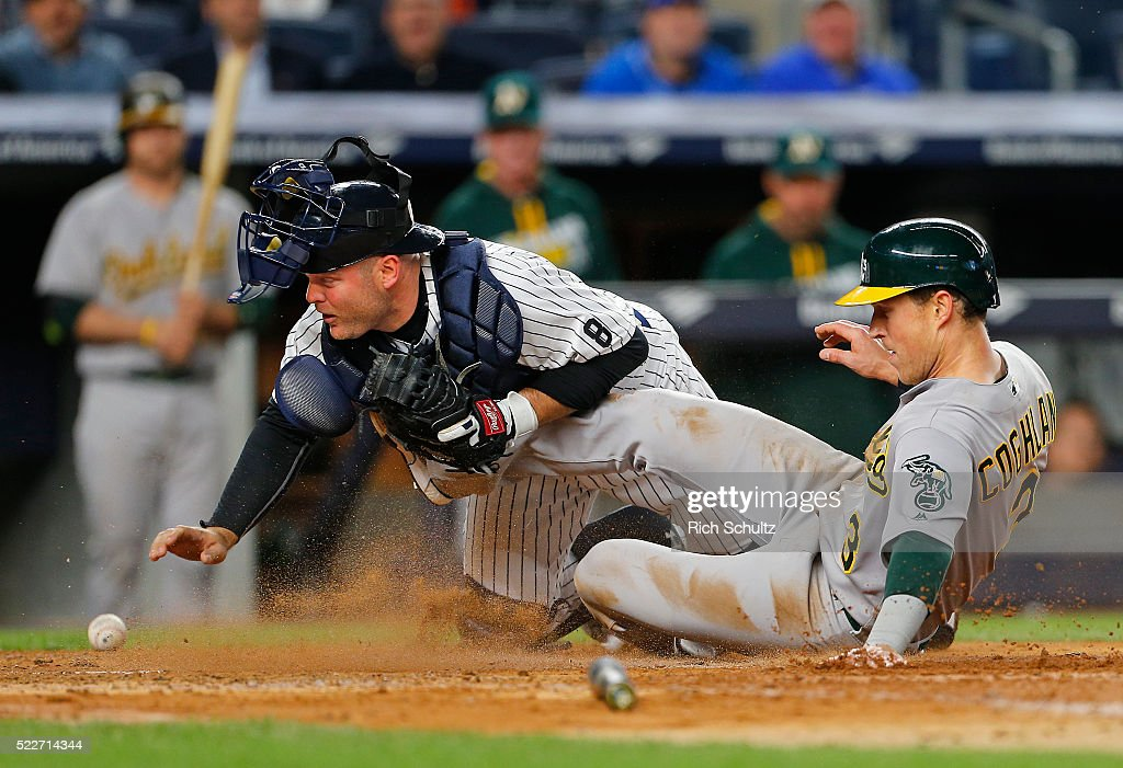 Chris Coghlan #3 of the Oakland Athletics scores on a double by Josh Reddick #22 as catcher Brian McCann #34 of the New York Yankees reaches back for the ball during the fourth inning of a game at Yankee Stadium on April 20, 2016 in the Bronx borough of New York City.