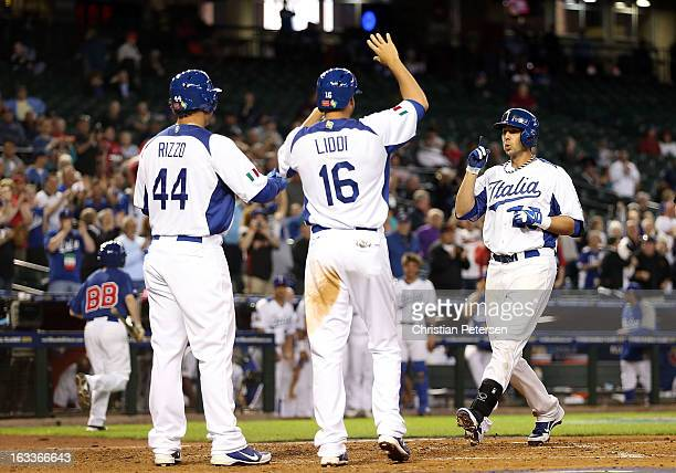 Chris Colabello of Italy is congratulated by Anthony Rizzo and Alex Liddi after Colabello hit a threerun home run against Canada during the third...
