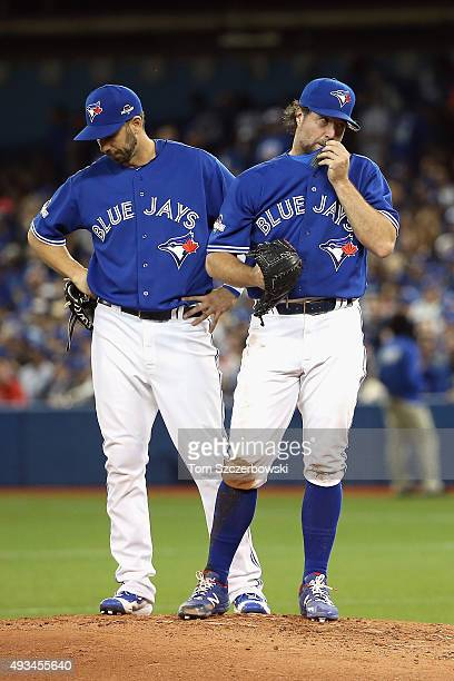Chris Colabello of the Toronto Blue Jays and RA Dickey of the Toronto Blue Jays wait on the pitcher's mound for manager John Gibbons of the Toronto...