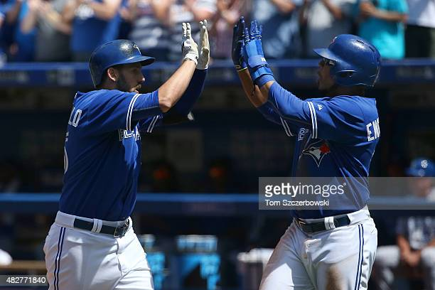 Chris Colabello of the Toronto Blue Jays is congratulated by Edwin Encarnacion after hitting a tworun home run in the fourth inning during MLB game...