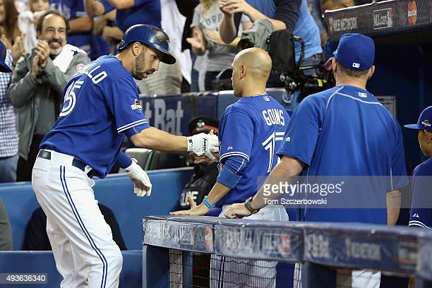 Chris Colabello of the Toronto Blue Jays is congratulated by Ryan Goins of the Toronto Blue Jays after hitting a solo home run in the second inning...