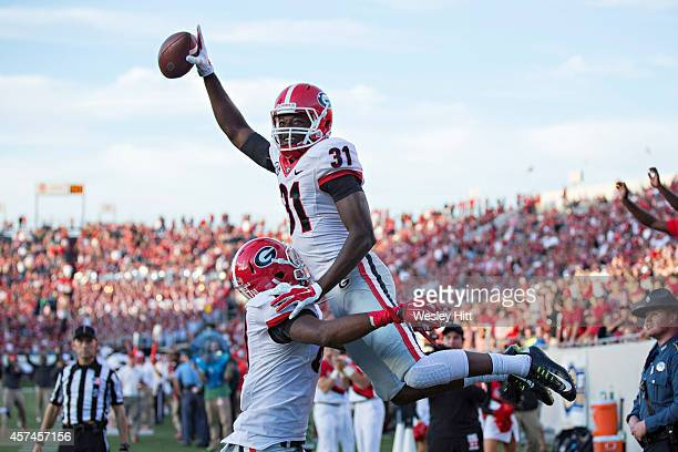 Chris Conley of the Georgia Bulldogs is lifted in the air after scoring a touchdown against the Arkansas Razorbacks at War Memorial Stadium on...