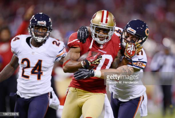 Chris Conte and Kelvin Hayden of the Chicago Bears defend against Kyle Williams of the San Francisco 49ers after Williams reception in the first...
