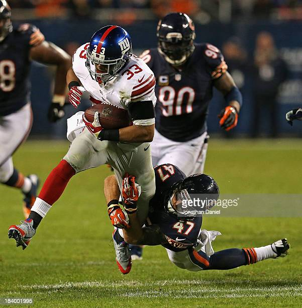 Chris Conte of the Chicago Bears tackles Da'Rel Scott of the New York Giants at Soldier Field on October 10 2013 in Chicago Illinois The Bears...