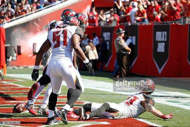 Chris Conte of the Tampa Bay Buccaneers celebrates with teammates in the end zone after returning an interception 20 yards for a touchdown against...