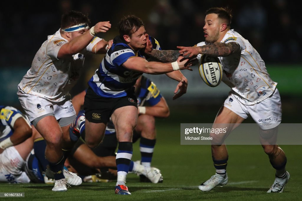Chris Cook of Bath offloads as he is tackled by Francois Hougaard (R) and GJ van Velze (L) of Worcester during the Aviva Premiership match between Worcester Warriors and Bath Rugby at Sixways Stadium on January 5, 2018 in Worcester, England.