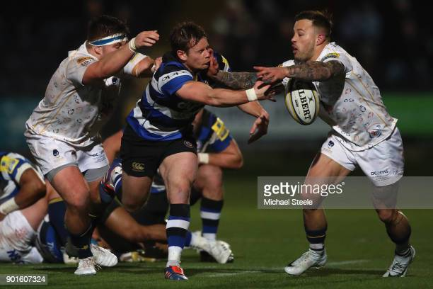 Chris Cook of Bath offloads as he is tackled by Francois Hougaard and GJ van Velze of Worcester during the Aviva Premiership match between Worcester...
