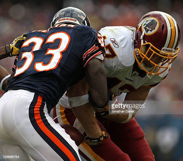 Chris Cooley of the Washington Redskins fumbles the ball as he is hit by Charles Tillman of the Chicago Bears at Soldier Field on October 24 2010 in...