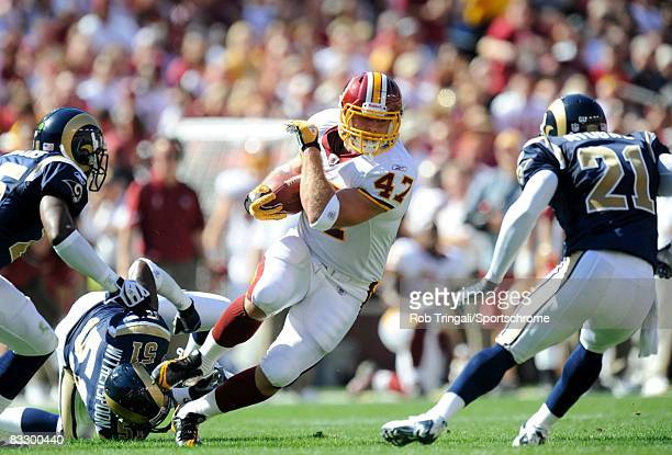 Chris Cooley of the Washington Redskins runs with the ball as Will Witherspoon the St. Louis Rams defends at FedEx Field on October 12, 2008 in...