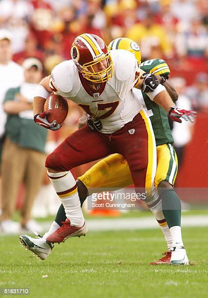 Chris Cooley of the Washington Redskins struggles to break a tackle against the Green Bay Packers at FedEx Field on October 31 2004 in Landover...