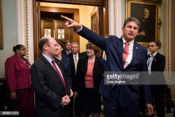 Chris Coons and Sen Joe Manchin emerge from the Senate floor after the Senate passed a procedural vote for a continuing resolution to fund the...