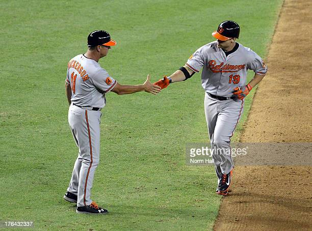 Chris Davis and third base coach Bobby Dickerson of the Baltimore Orioles celebrate Davis' home run against the Arizona Diamondbacks at Chase Field...