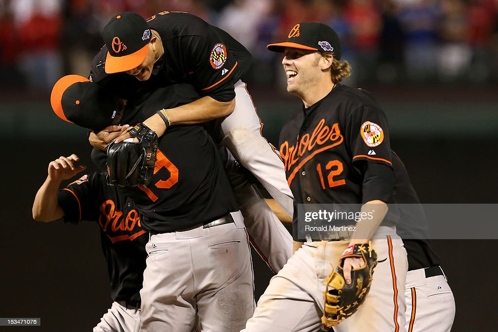 Chris Davis #19, Manny Machado #13 Mark Reynolds #12 of the Baltimore Orioles celebrate after they won 5-1 against the Texas Rangers during the American League Wild Card playoff game at Rangers Ballpark in Arlington on October 5, 2012 in Arlington, Texas.