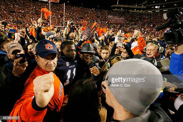 Chris Davis of the Auburn Tigers is surrounded after scoring the winning touchdown to defeat the Alabama Crimson Tide 34 to 28 at JordanHare Stadium...