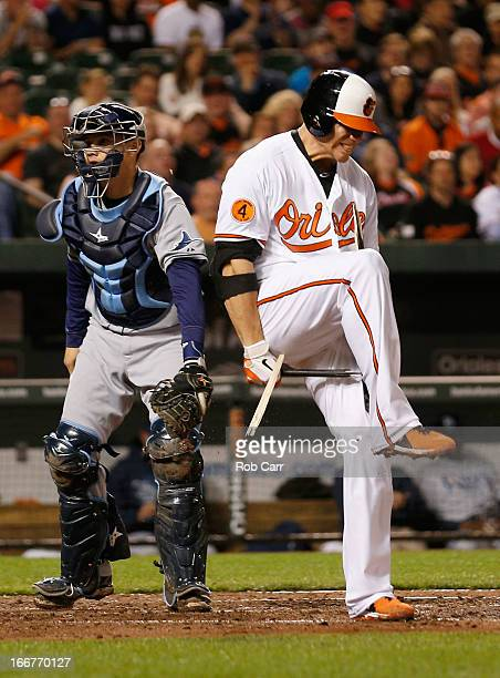 Chris Davis of the Baltimore Orioles breaks his bat after striking out to end the third inning as catcher Jose Lobaton of the Tampa Bay Rays looks on...