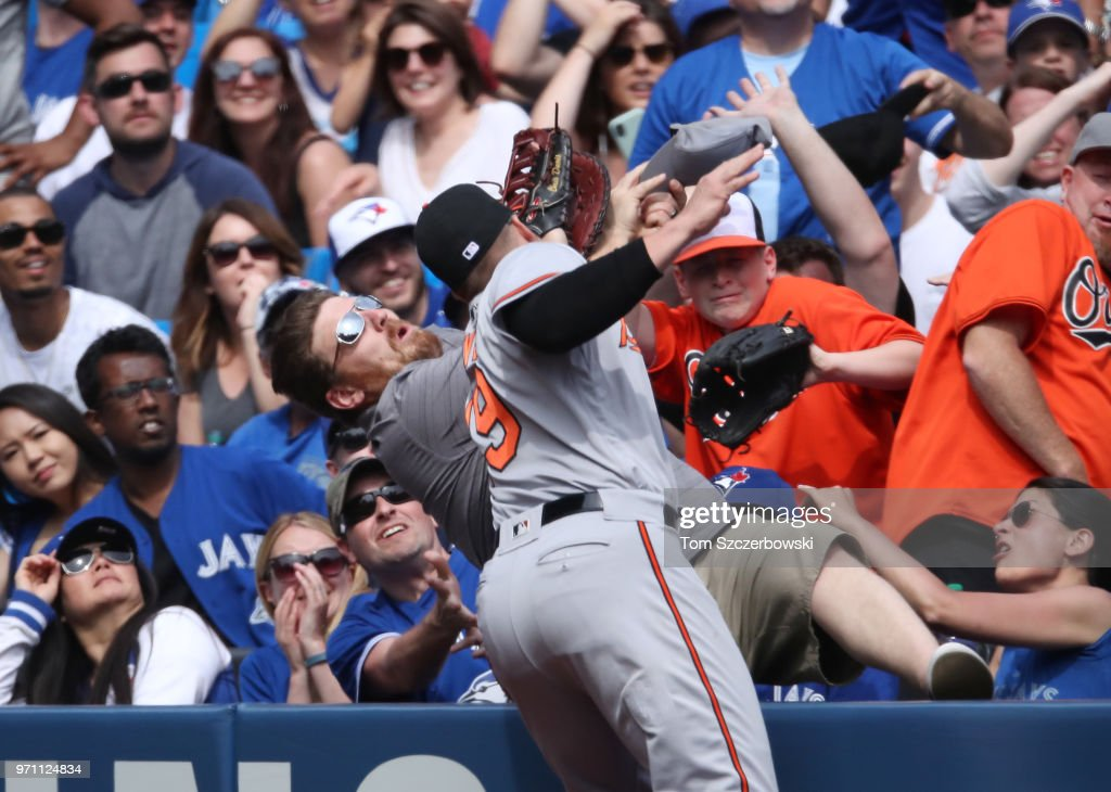 Chris Davis #19 of the Baltimore Orioles cannot get to a foul pop up that lands out of play as a fan falls over in the eighth inning during MLB game action against the Toronto Blue Jays at Rogers Centre on June 10, 2018 in Toronto, Canada.