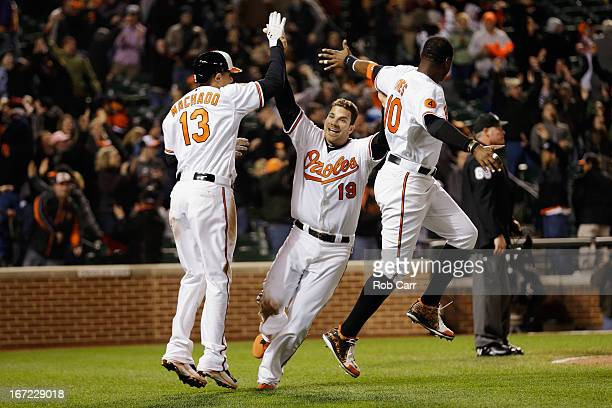 Chris Davis of the Baltimore Orioles celebrates scoring the game winning run with Manny Machado and Adam Jones during the Orioles 2-1 win over the...