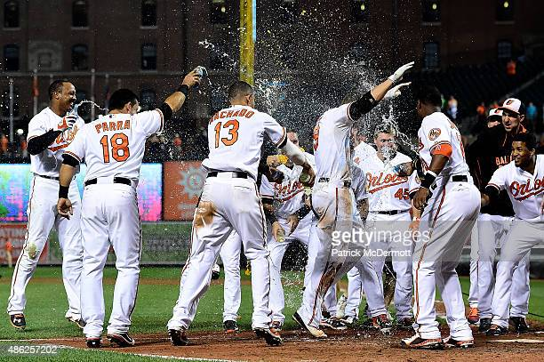 Chris Davis of the Baltimore Orioles celebrates with his teammates as he crosses home plate after hitting the game winning home run in the eleventh...