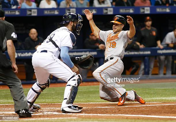 Chris Davis of the Baltimore Orioles crosses home plate ahead of catcher Curt Casali of the Tampa Bay Rays to score off of a single by Mark Trumbo...