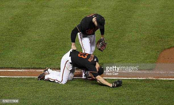 Chris Davis of the Baltimore Orioles helps up pitcher Zach Britton after Britton tagged out a runner for the last out of the ninth inning during the...