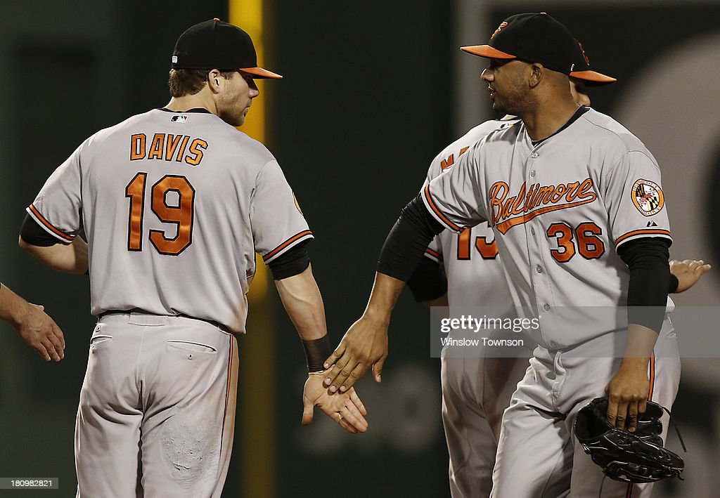Chris Davis #19 of the Baltimore Orioles is congratulated by Chris Dickerson #36 of the Baltimore Orioles after their 5-3 win over the Boston Red Sox at Fenway Park on September 18, 2013 in Boston, Massachusetts.