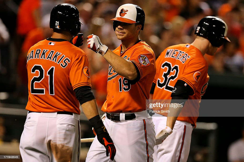 Chris Davis #19 of the Baltimore Orioles is congratulated by teammate Nick Markakis #21 after hitting a two-run home run against the New York Yankees in the sixth inning at Oriole Park at Camden Yards on June 29, 2013 in Baltimore, Maryland. The Baltimore Orioles won, 11-3.