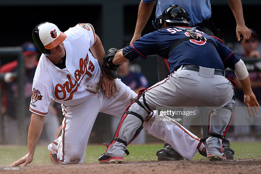 Chris Davis #19 of the Baltimore Orioles is tagged by catcher Kurt Suzuki #8 of the Minnesota Twins in the seventh inning at Oriole Park at Camden Yards on September 1, 2014 in Baltimore, Maryland. The Minnesota Twins won, 6-4.