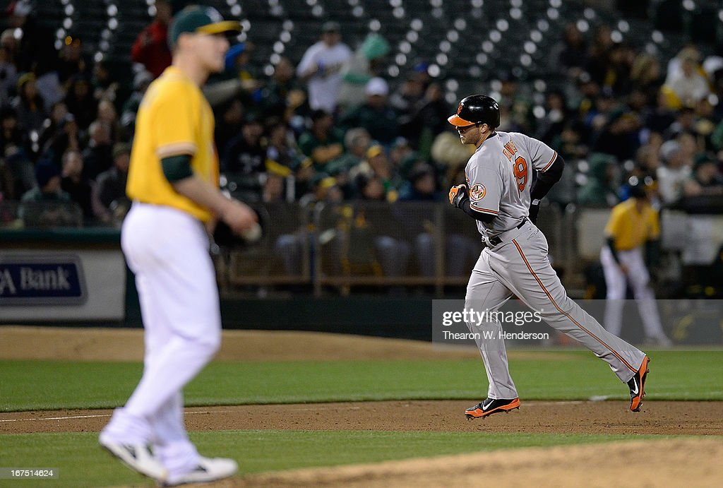 Chris Davis #19 of the Baltimore Orioles rounds the bases after hitting a solo home run as pitcher Jarrod Parker #11 of the Oakland Athletics walks to the mound in the fifth inning at O.co Coliseum on April 25, 2013 in Oakland, California.
