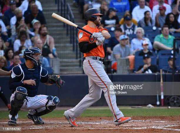 Chris Davis of the Baltimore Orioles singles for an rbi in the second inning during the spring training game against the New York Yankees at...