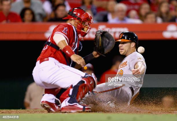 Chris Davis of the Baltimore Orioles slides safely past catcher Hank Conger of the Los Angeles Angels of Anaheim and scores a run in the sixth inning...