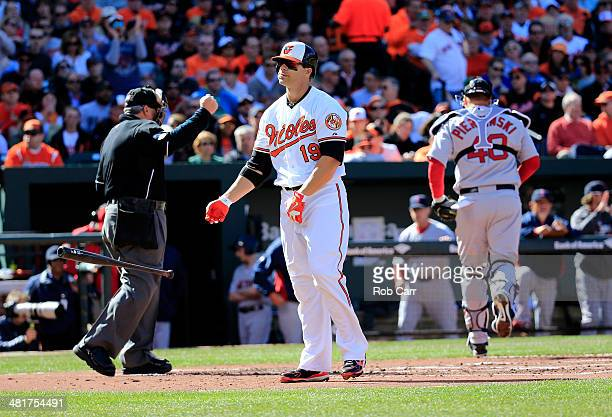 Chris Davis of the Baltimore Orioles tosses his bat after striking out for the third out of the first inning of Opening Day as home plate umpire Dana...