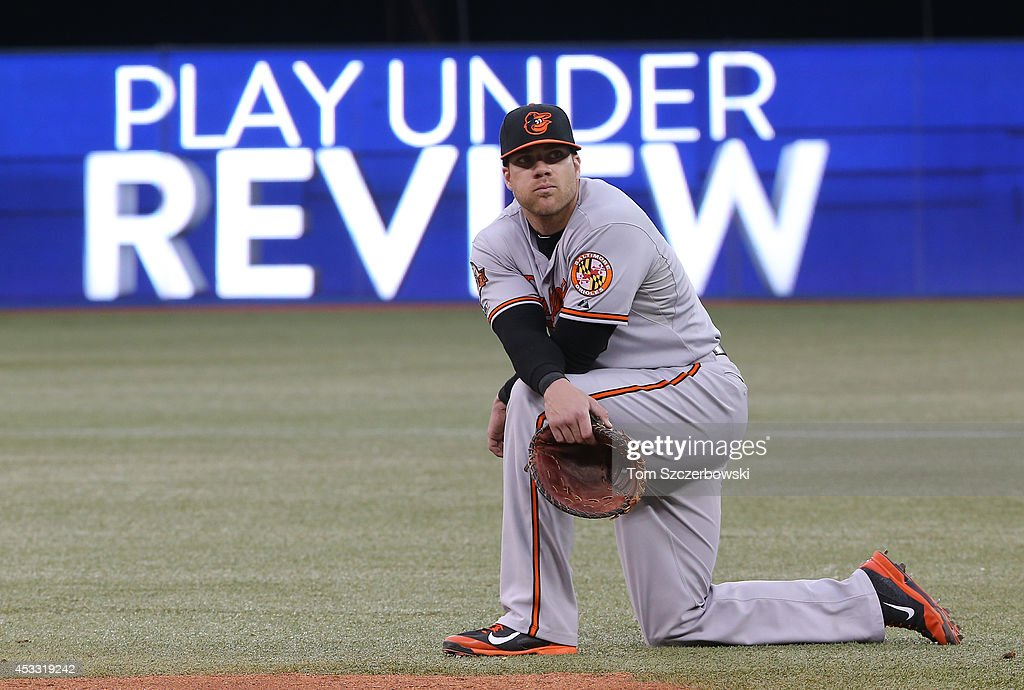 Chris Davis #19 of the Baltimore Orioles waits as a play is reviewed by video in the third inning during MLB game action against the Toronto Blue Jays on August 7, 2014 at Rogers Centre in Toronto, Ontario, Canada.