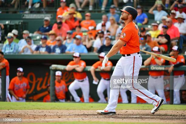 Chris Davis of the Baltimore Orioles watches the ball after hitting a sacrifice fly to right during the sixth inning of a Grapefruit League spring...