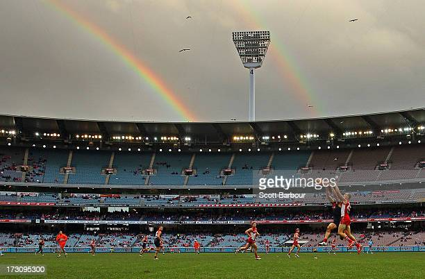 Chris Dawes of the Demons and Ted Richards of the Swans compete for the ball as a double rainbow appears above the ground during the round 15 AFL...