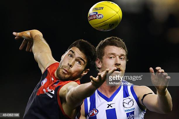Chris Dawes of the Demons competes for the ball against Lachlan Hansen of the Kangaroos during the round 23 AFL match between the North Melbourne...