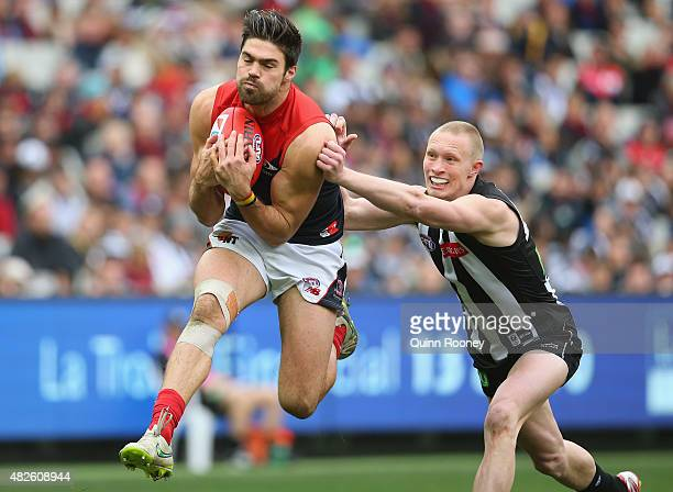 Chris Dawes of the Demons marks infront of Jack Frost of the Magpies during the round 18 AFL match between the Collingwood Magpies and the Melbourne...