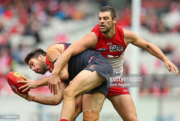 Chris Dawes of the Demons takes a mark in front of Heath Grundy of the Swans during the round 15 AFL match between the Melbourne Demons and the...