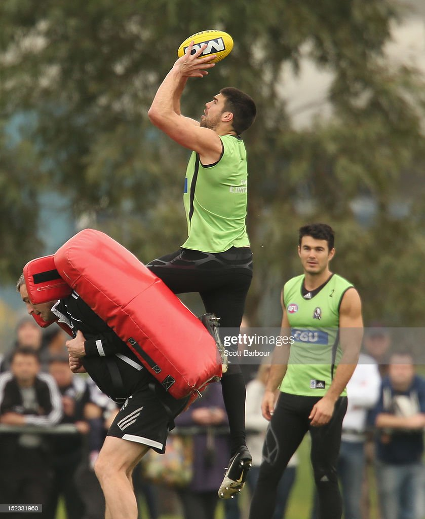 Chris Dawes of the Magpies is watched by Chris Tarrant as he marks the ball during a Collingwood Magpies AFL training session at Gosch's Paddock on September 19, 2012 in Melbourne, Australia.