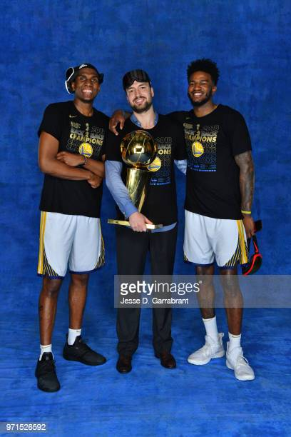 Chris DeMarco Jordan Bell and Kevon Looney of the Golden State Warriors pose for a portrait with the Larry O'Brien Trophy after winning Game Four of...