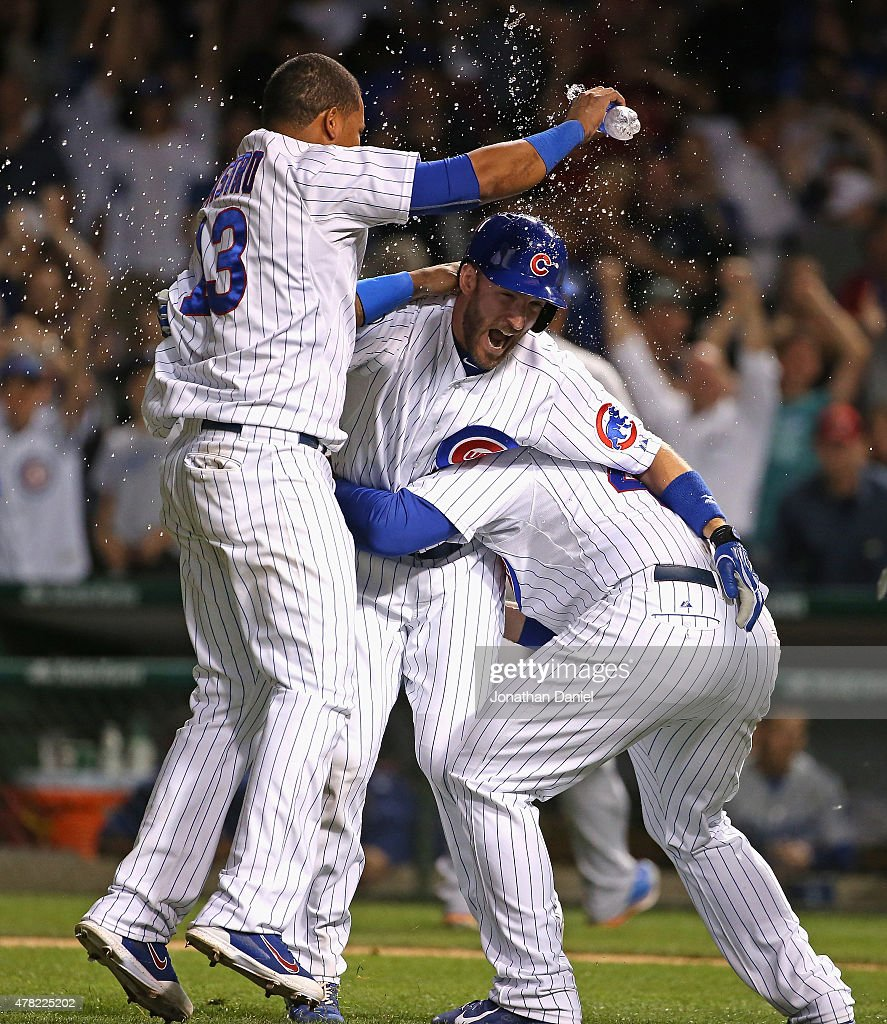 Chris Denorfia #15 of the Chicago Cubs (center) celebrates with Starlin Castro #13 (L) and Anthony Rizzo #44 (R) after hitting a sacrifice fly to score the winning run against the Los Angeles Dodgers at Wrigley Field on June 23, 2015 in Chicago, Illinois. The Cubs defeated the Dodgers 1-0 in 10 innings.