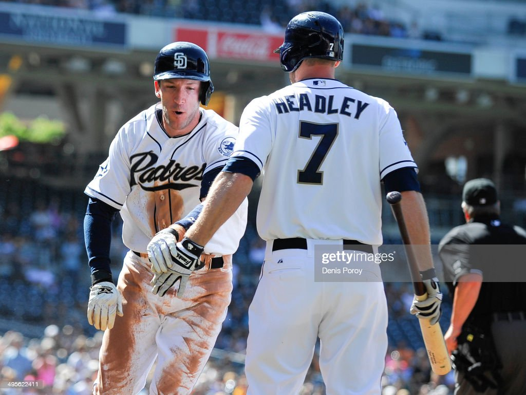 Chris Denorfia #13 of the San Diego Padres is congratulated by Chase Headley #7 after scoring during the first inning of a baseball game against the Pittsburgh Pirates at Petco Park June 4, 2014 in San Diego, California.