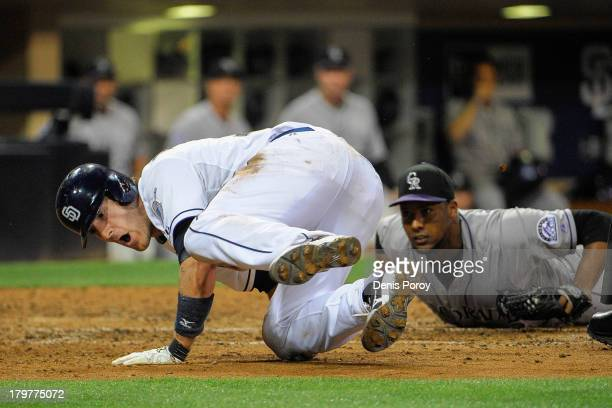 Chris Denorfia of the San Diego Padres slides after scoring ahead of the tag by Juan Nicasio of the Colorado Rockies during the sixth inning of a...