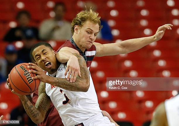 Chris Denson of the Auburn Tigers draws a foul from Brian Steele of the South Carolina Gamecocks during the first round of the SEC Men's Basketball...