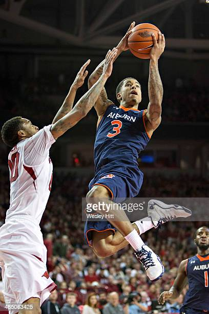 Chris Denson of the Auburn Tigers goes to the basket against Rashad Madden of the Arkansas Razorbacks at Bud Walton Arena on January 25, 2014 in...