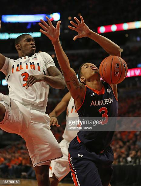 Chris Denson of the Auburn Tigers looses control of the ball under pressure from Brandon Paul of the Illinois Fighting Illini at United Center on...