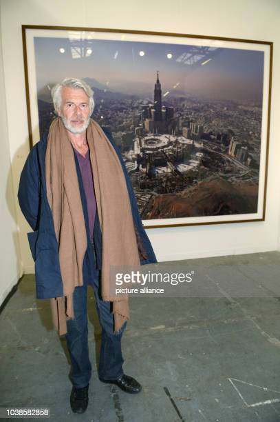Chris Dercon Director der Tate Gallery of Modern Art poses in front of a work by artist Ahmed Mater depicting the city of Mecca during the art fair...