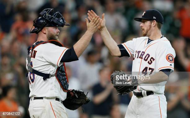 Chris Devenski of the Houston Astros high fives catcher Brian McCann after the final out against the Los Angeles Angels of Anaheim at Minute Maid...